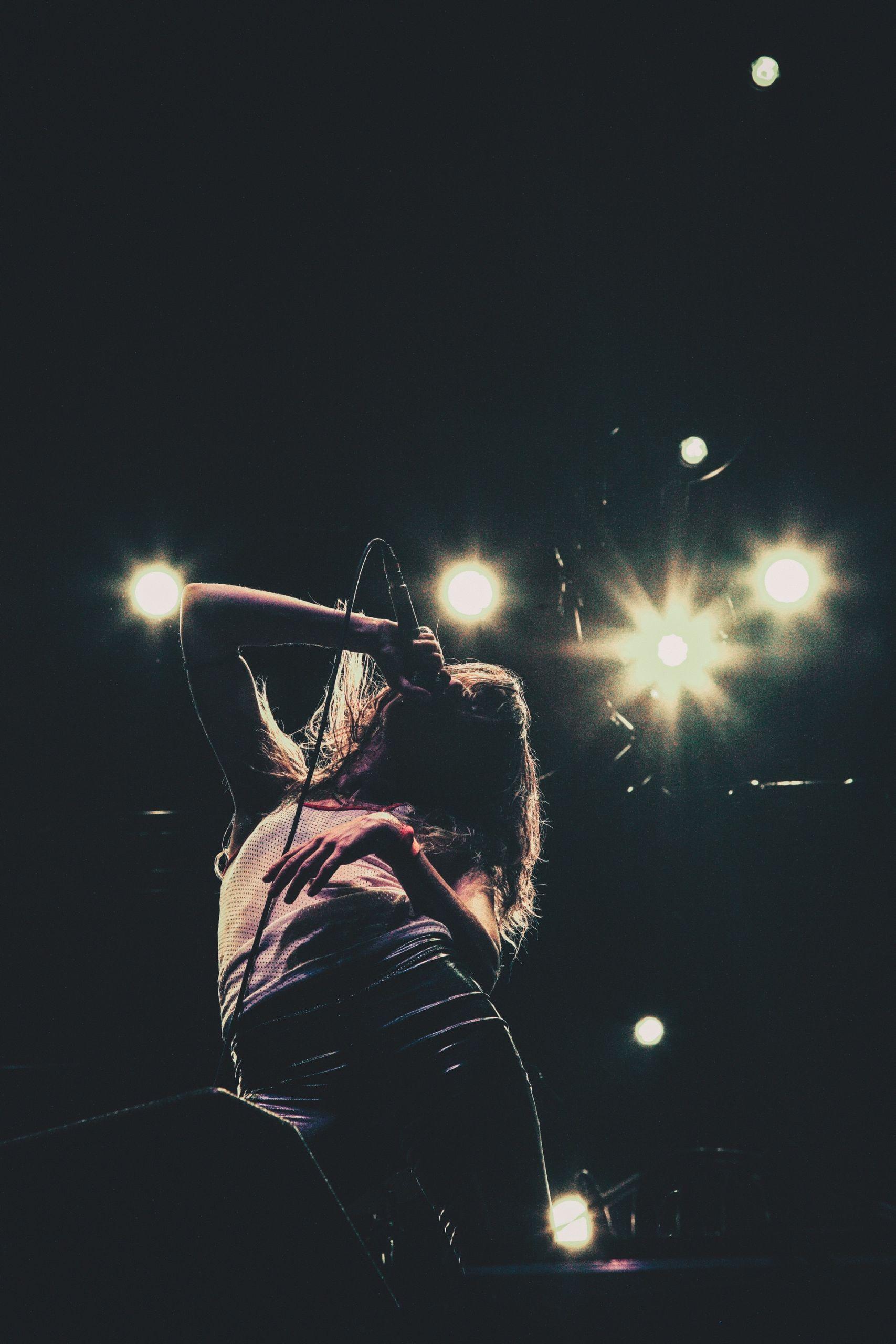 Eine Person in der Dunkelheit unter einzelnen grellen Lichtern, singt in ein Microphone.