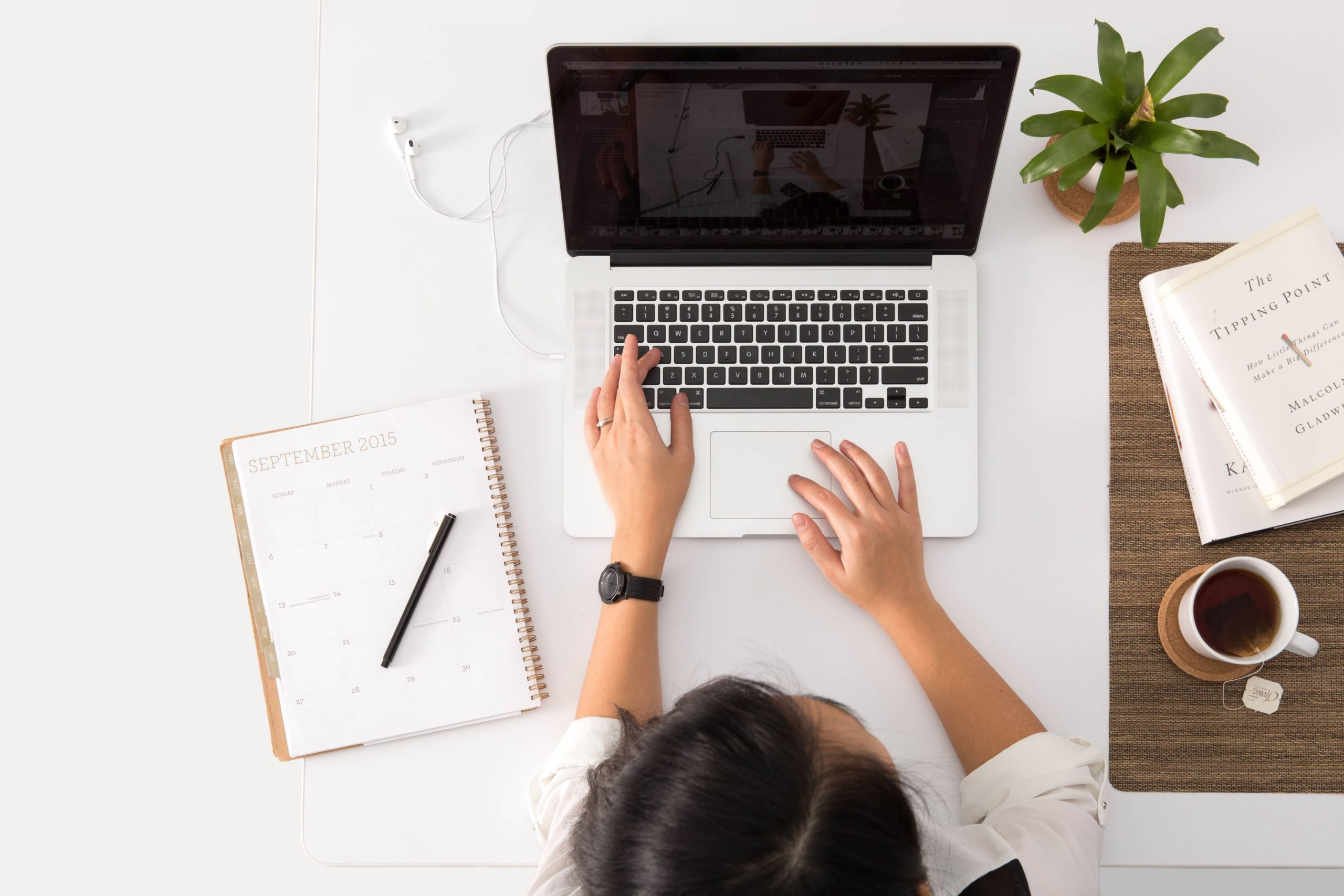 Person sitzt an einem Laptop. Um den Laptop herum befinden sich verschiedene Dokumente, eine Tasse Kaffee und eine Pflanze. Der Blickwinkel ist von oben.