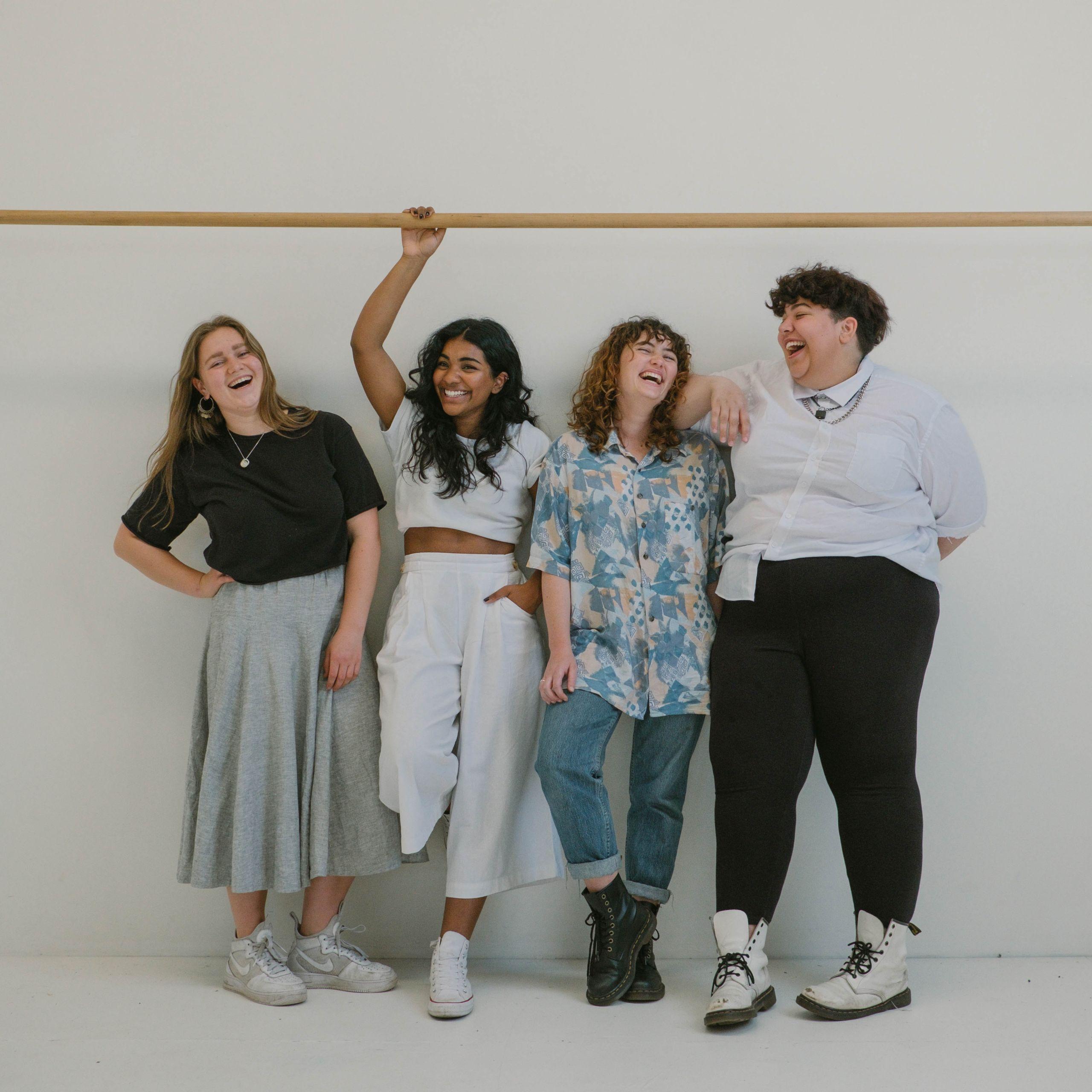 vier Personen stehen nebeneinader vor einer Wand und lachen.