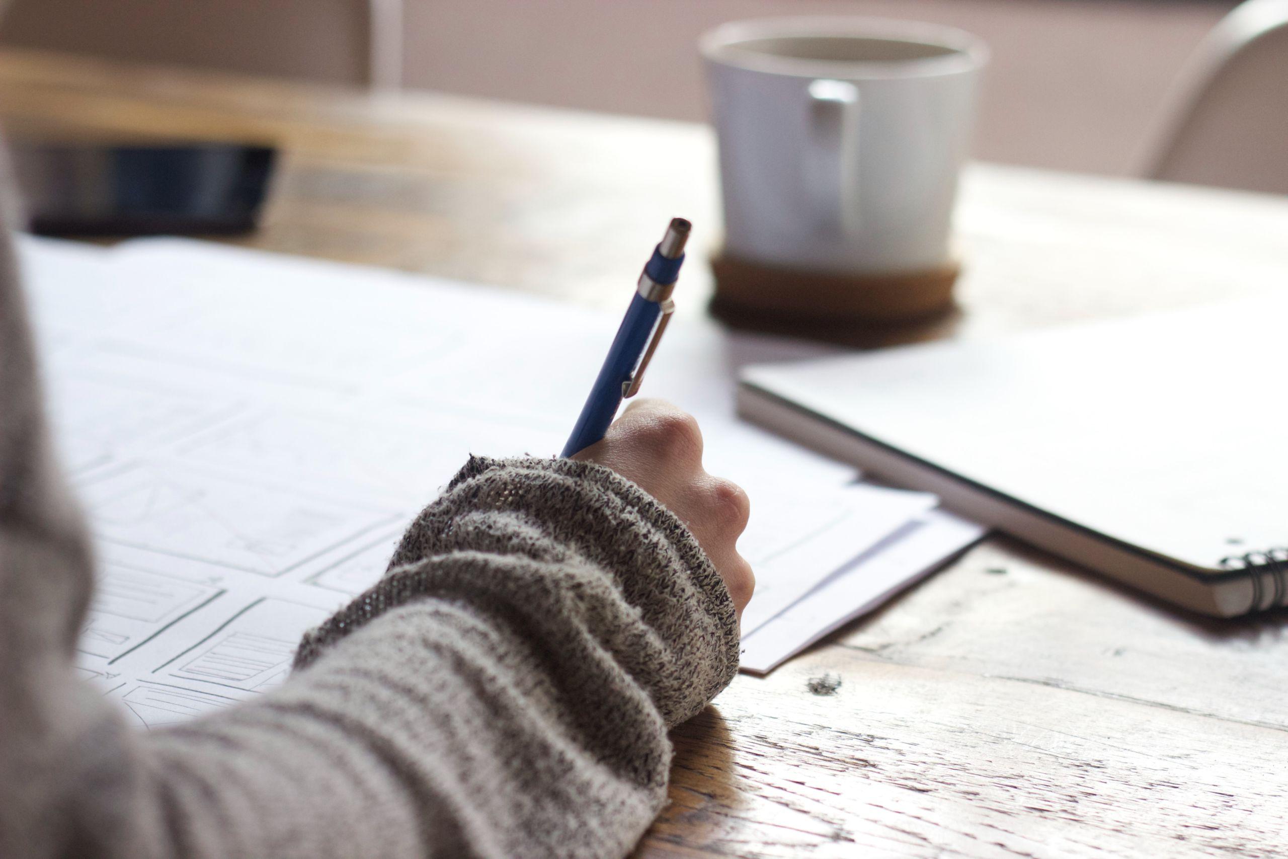 Auf einem Holztisch, liegen mehrere Blätter, ein Block und eine Tasse. Eine Person schreibt mit einem Stift auf eines der Blätter.