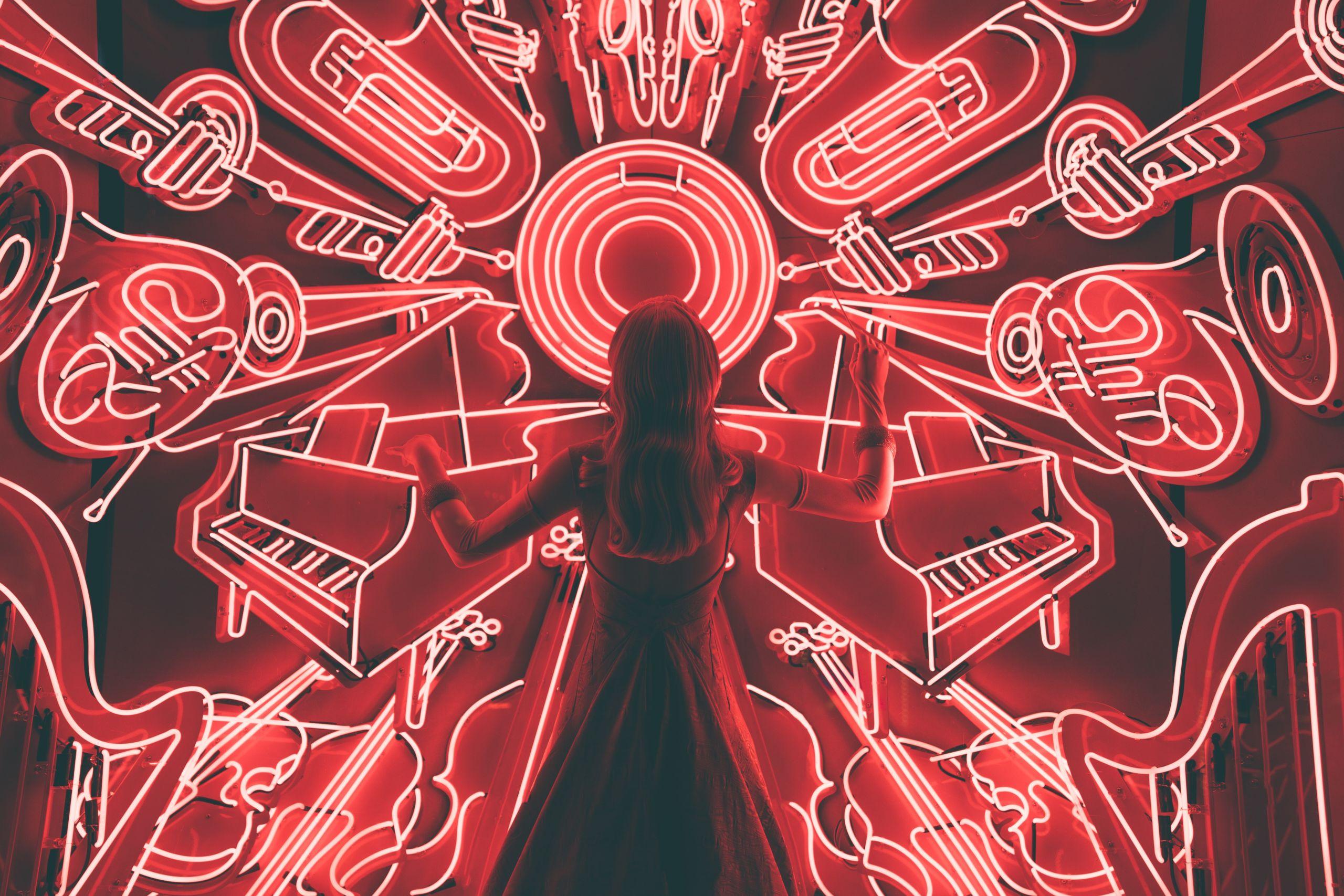 Eine Person steht vor einer Wand mit leuchtenden, gemalten Instrumenten, die rot leuchten.
