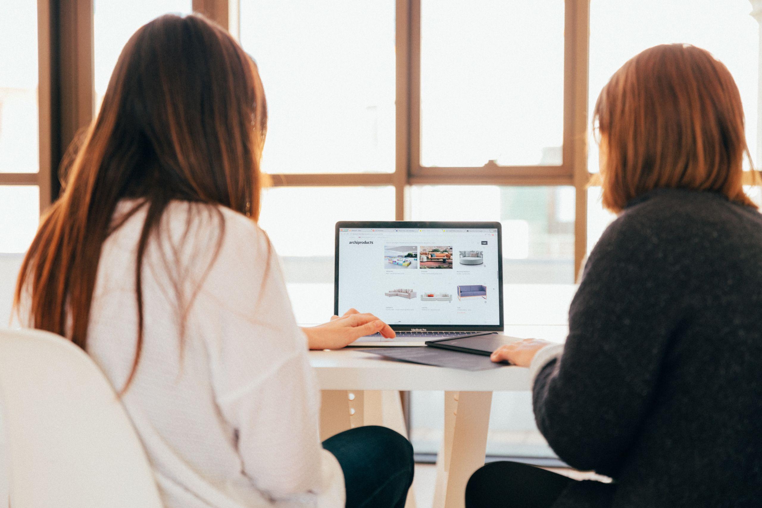 Zwei als Frauen* gelesene Personen sitzen gemeinsam vor einem Laptop vor einer großen Fensterfront.