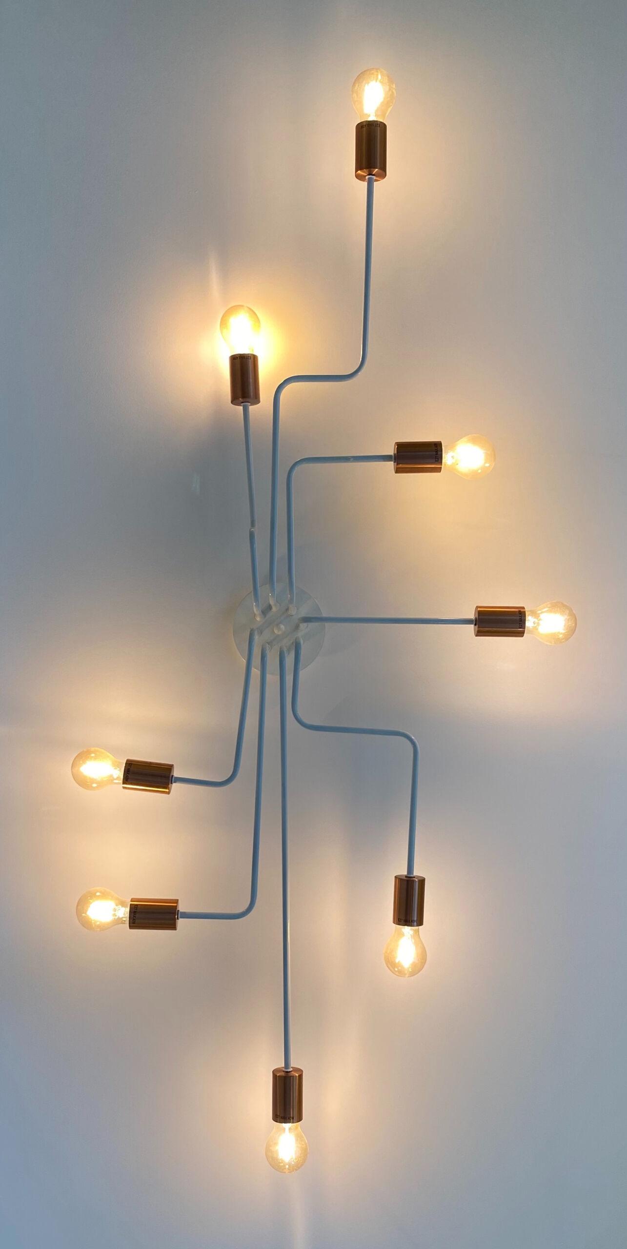 An einer Wand hängt eine Lampe, die acht Arme und am Ende jeweils eine Glühbirne hat.