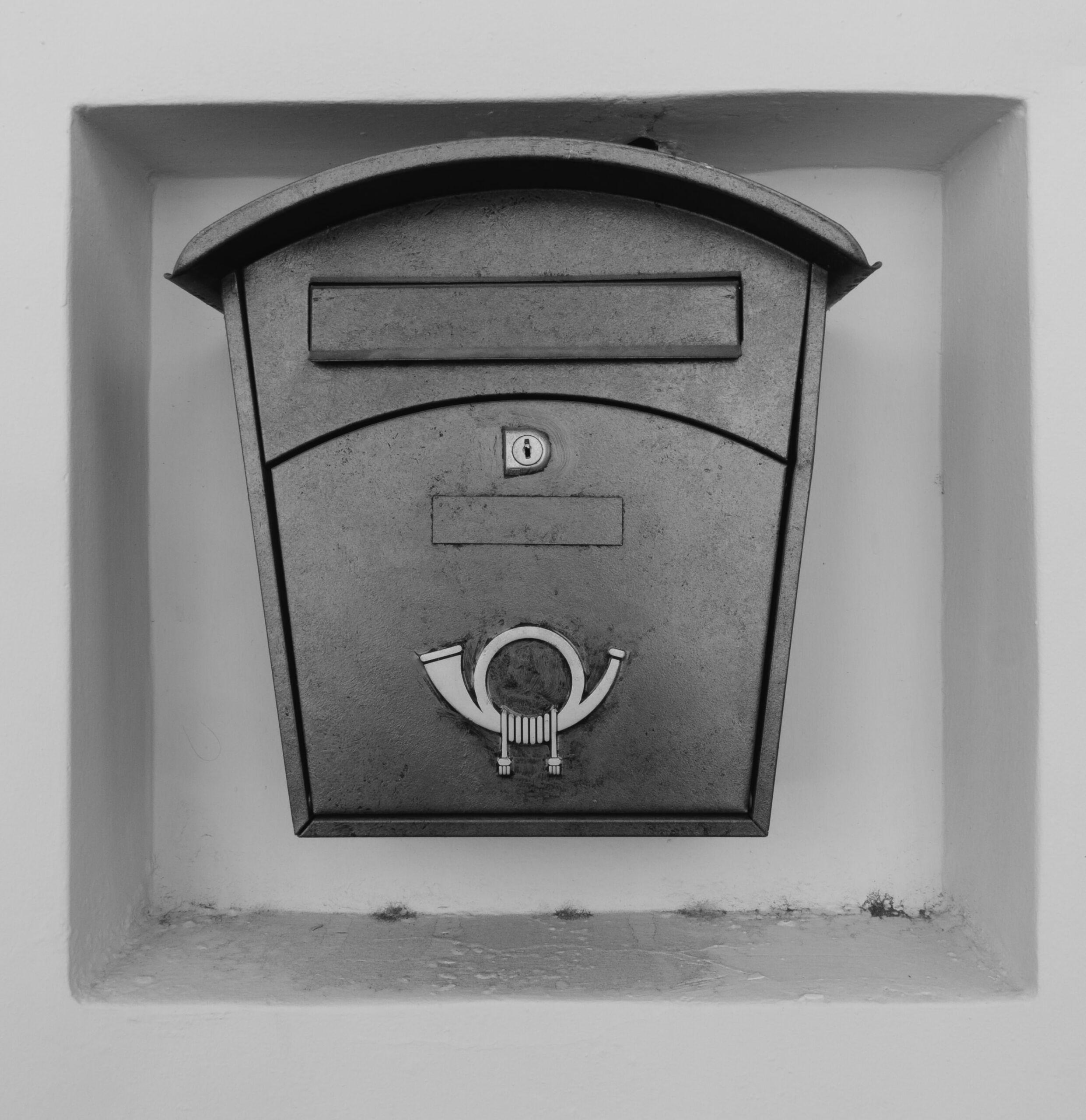 Ein schwarz-weiß Bild eines Briefkastens mit dem Zeichen der Post