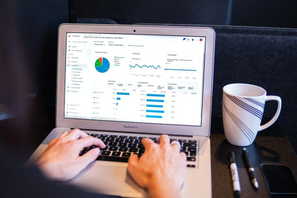 Auf einem Laptop sind Graphiken zu sehen. Neben dem Laptop steht eine Tasse und davor liegen zwei Stifte. An der Tastatur des Laptops sind Hände zu sehen, die vermutlich Tippen.